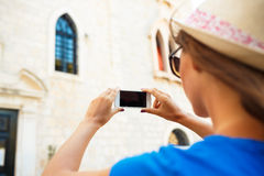 Girl in hat making photos of a church by the smartphone Royalty Free Stock Images