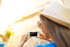Girl in hat making photos of a church by the smartphone Stock Image