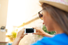 Girl in hat making photos of a church by the smartphone Royalty Free Stock Photography