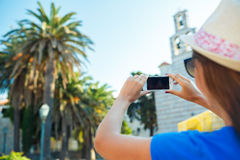 Girl in hat making photos of a church by the smartphone Royalty Free Stock Photos