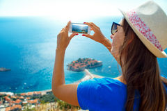 Girl in the hat making photos by the smartphone near the island Royalty Free Stock Image