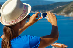 Girl in hat making photos of the smartphone Perast in Boka Kotor Stock Photo
