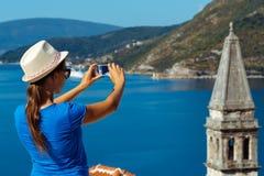 Girl in hat making photos of the smartphone Perast in Boka Kotor. Bay, Montenegro, Balkans Royalty Free Stock Images