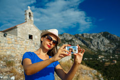 Girl in the hat making selfie by the smartphone on the backgroun Royalty Free Stock Photography