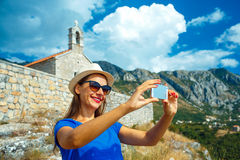Girl in the hat making selfie by the smartphone on the backgroun Stock Photos