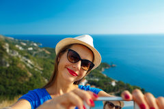 Girl in the hat making selfie by the smartphone on the backgroun Royalty Free Stock Photo