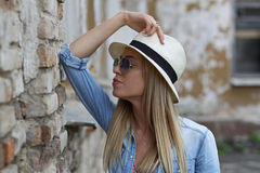 Girl in a hat near a brick wall royalty free stock photos