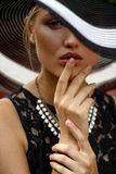 The girl in the hat and necklace. Portrait of the girl with a hat, a necklace and a black lace dress Stock Photography