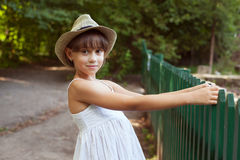 Girl in the hat next to a fence Stock Photo