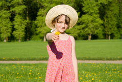 The girl in the hat offers a flower Royalty Free Stock Photos