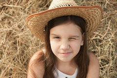 Girl in the hat with one closed eye. Little girl in the straw hat with one closed eye on the hay backgraund Stock Image