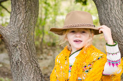 Girl with hat and orange pelerine in autumn season Royalty Free Stock Images