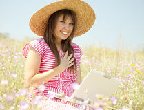 Girl in hat at the park with computer. Royalty Free Stock Photos