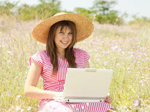 Girl in hat at the park with computer. Royalty Free Stock Images