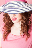 The girl in the hat on a pink background pinup. Girl pinup-style in a pink dress with hat with brim Stock Photos