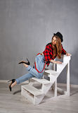 The girl in a hat, plaid shirt and jeans Royalty Free Stock Photography