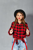The girl in a hat, plaid shirt and jeans Stock Photo