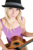 Girl with hat, playing an acoustic guitar Stock Photos