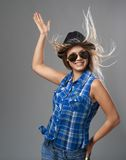 Girl in a hat pointing up and her hair flutter Royalty Free Stock Photography