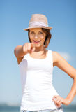 Girl in hat pointing at you on the beach Stock Images