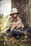 Girl in a hat reading a book in autumn forest Royalty Free Stock Image