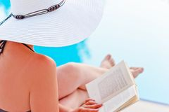 Girl in a hat reading a book near the pool, sitting in a lounge chair Royalty Free Stock Photography