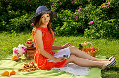 Girl in a hat reading a magazine on the nature. Picnic, the girl in a hat reading a magazine Royalty Free Stock Photo