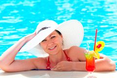 Girl in a hat relaxes in the pool Stock Image