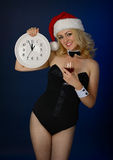 Girl in the hat of Santa Claus with a clock Royalty Free Stock Photo