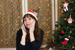 The girl in the hat of Santa Claus talking on the phone. Congratulation to the holiday on the phone. Christmas Eve royalty free stock photo