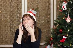 The girl in the hat of Santa Claus talking on the phone. Congratulation to the holiday on the phone. Christmas Eve stock photos