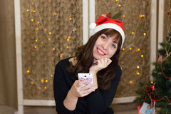 The girl in the hat of Santa Claus talking on the phone. Congratulation to the holiday on the phone. Christmas Eve stock image