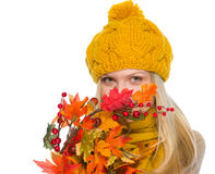Girl in hat and scarf hiding behind autumn bouquet Royalty Free Stock Photography