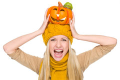 Girl in hat and scarf with jack-o-lantern on head Stock Photography