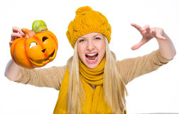 Girl in hat and scarf scaring with jack-o-lantern. Isolated on white Stock Photo