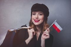 Girl in hat with shopping bags and flag of Poland. Style redhead girl in hat with shopping bags and flag of Poland on grey background Royalty Free Stock Photography