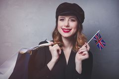 Girl in hat with shopping bags and flag of United Kingdom Stock Photos
