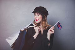 Girl in hat with shopping bags and flag of United Kingdom Royalty Free Stock Photo