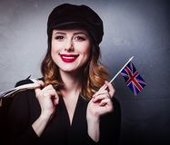 Girl in hat with shopping bags and flag of United Kingdom. Style redhead girl in hat with shopping bags and flag of United Kingdom on grey background stock images