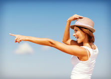 Girl in hat showing direction on the beach Stock Image