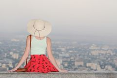 Girl in hat sits and looks at the city from a height. Rear view, evening time Stock Photography