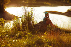 Girl in hat sitting on the bank of the river Stock Image