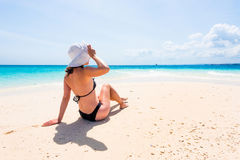 Girl in hat sitting on beautiful beach Royalty Free Stock Photos