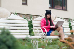 Girl in a hat sitting on a bench Stock Photography