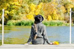 Girl in the hat sitting on the dock. Autumn forest. Back view.  Royalty Free Stock Photography