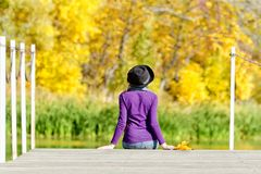 Girl in the hat sitting on the dock. Autumn forest. Back view.  Royalty Free Stock Photos