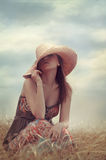 Girl in the field. Girl in a hat sitting in a field Royalty Free Stock Image