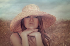 Girl in the field. Girl in a hat sitting in a field Royalty Free Stock Photography