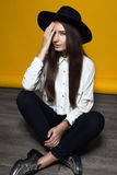 Girl in a hat sitting on the floor. Girl in a white blouse and a hat sitting on the floor on a yellow background Stock Image