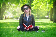 Girl in hat sitting on grass Royalty Free Stock Images